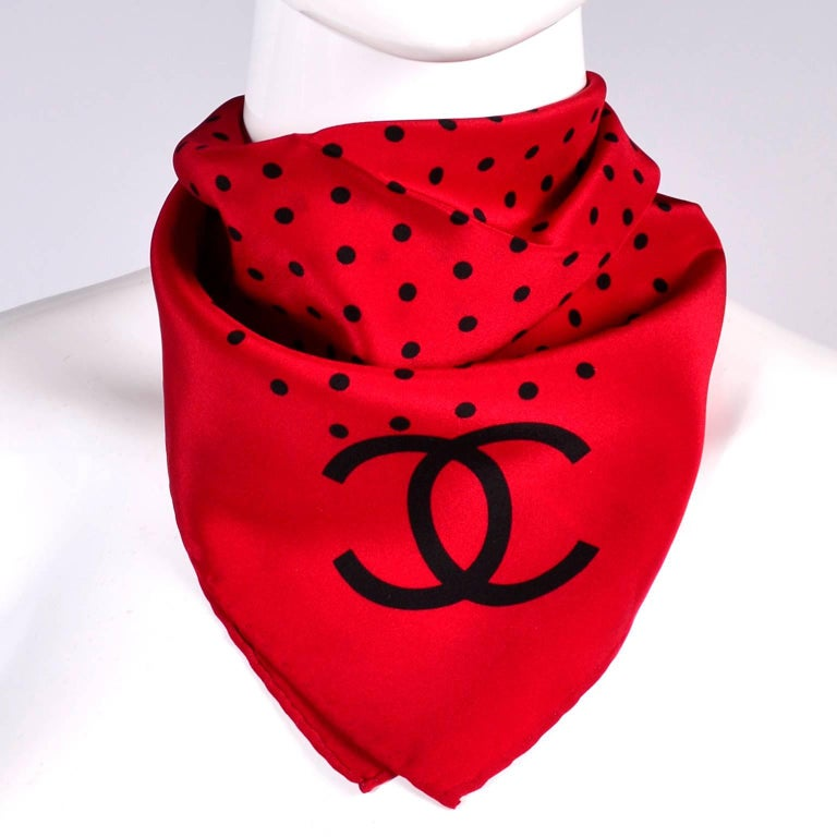This is a beautiful red silk Chanel scarf with black polka dots and the CC logo. This scarf would make a great gift and is a perfect neck scarf to wear under a jacket or blouse.