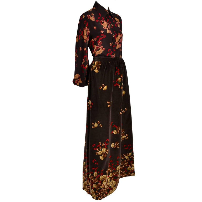 This is a beautiful 1970's Valentino outfit in an iconic acorn and red berry print with a silk blouse and a matching velvet maxi skirt by Valentino Boutique. The fully lined skirt is made of beautiful brown cotton velvet with subtle gathering at the