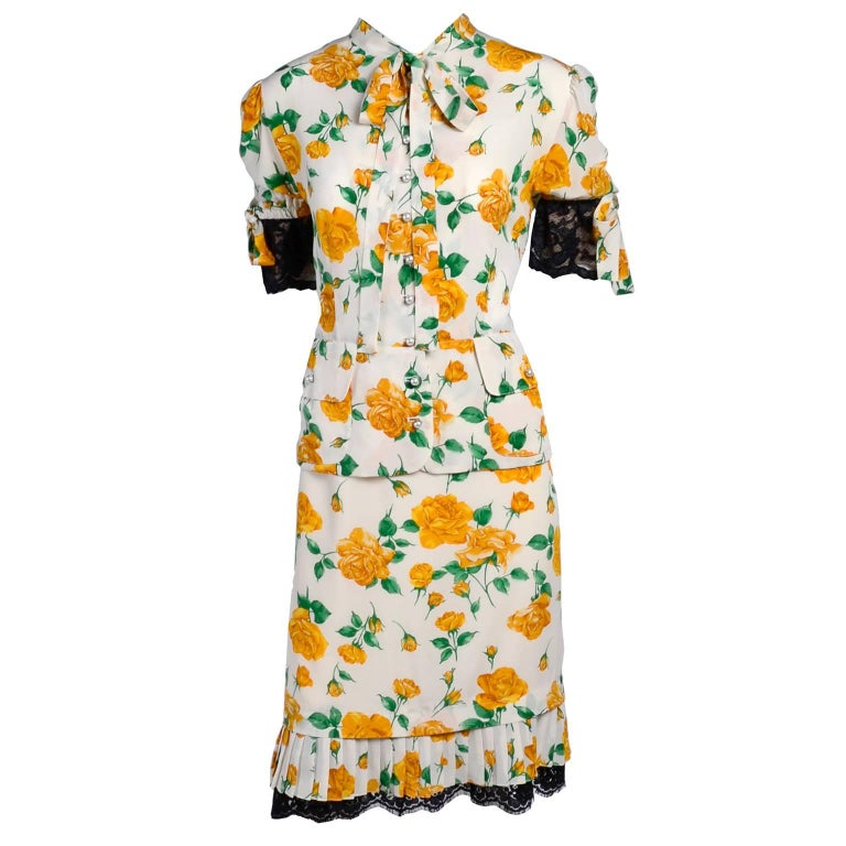 This two piece silk vintage 1990s Dolce & Gabbana dress has a skirt and blouse in a yellow rose print fabric with black lace trim.  The blouse has a slight peplum, a pussy bow, faux pearl buttons up the front, two front pockets and puff sleeves with