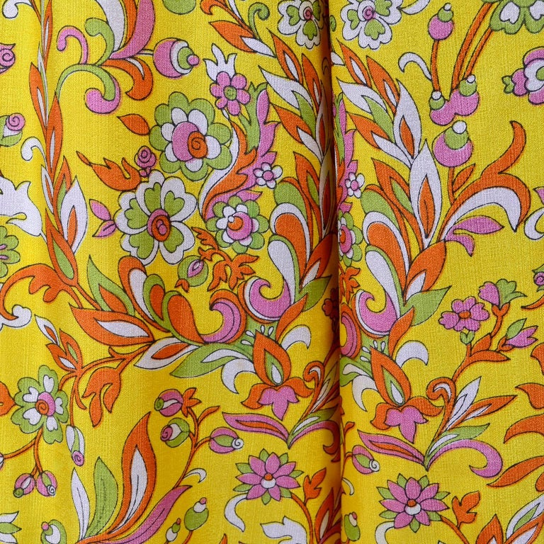 This is a vintage early 1970's Sea Isle fashions yellow, orange, green, pink and white jumpsuit with matching sash. The jumpsuit has wide leg palazzo pants, side slit pockets, and a back zipper. There is no fabric content label but if feels like a