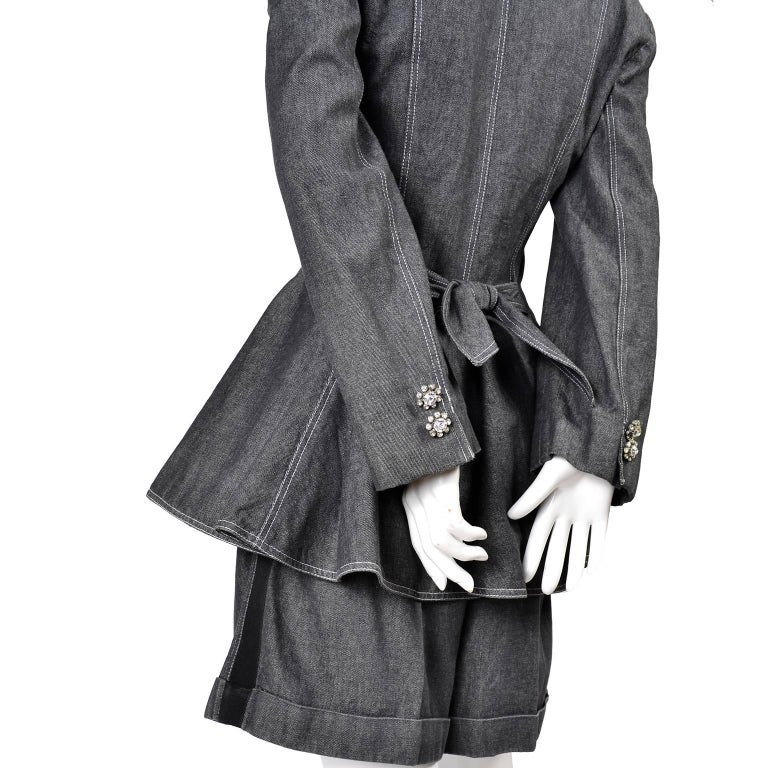 This Patrick Kelly grayed black denim vintage short and jacket suit was purchased at Printemp's in Denver in the mid 1980's. The jacket is cinched at the waist and closes with a single rhinestone button. The blazer has a sash that ties in the back,