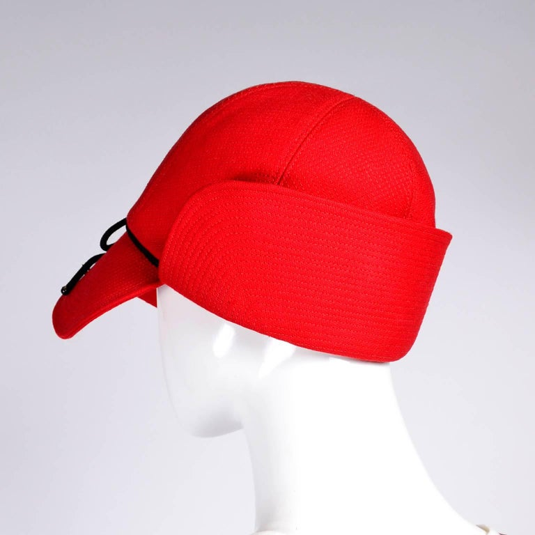 """This is a wonderful vintage YSL red flap cap with top stitching and black trim. The hat measures 22"""" in circumference on the inside rim and is labeled a size small. This hat is lined in red satin and is an unusual style - similar to a dear stalker"""