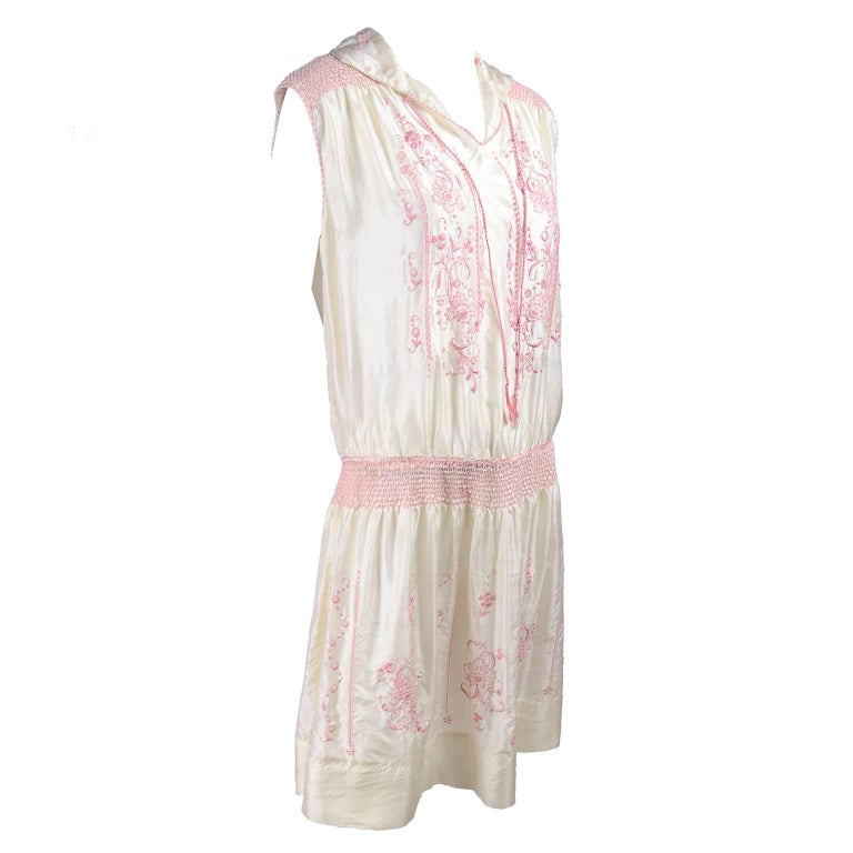 This is a beautiful ivory silk vintage dress from the late 1920's. The dress is sleeveless, with a pink silk braided tie at the neck and it is decorated with gorgeous pink embroidery, smock pleating, cutwork and topstitching.  We acquired the dress