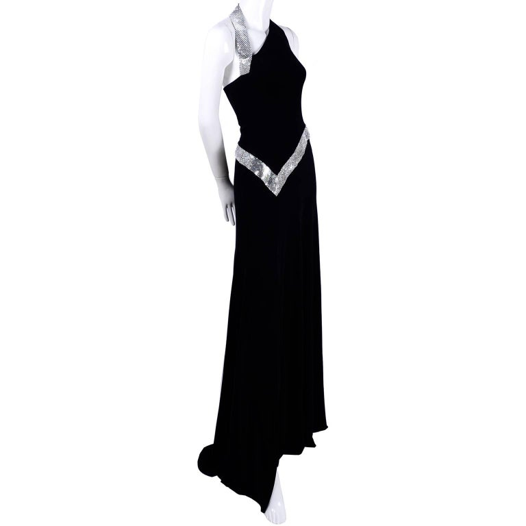 This is a show stopping vintage dress from Jiki of Monte Carlo that was made in France in the 1990's.  The dress is black crepe with a thigh high slit and is trimmed with absolutely gorgeous silver mesh alternated with crystal clear rhinestones. We