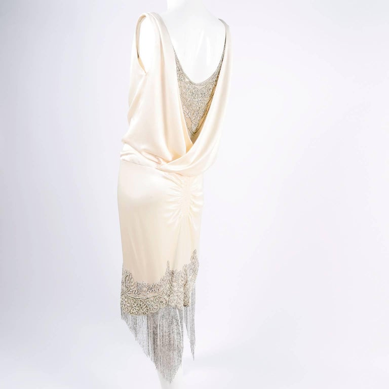 This is an exquisite creamy ivory silk dress designed by Alexander McQueen with exceptional hand beading.  Marked 2007, the silk charmeuse drapes at the neckline over a nude tulle net underlayer that is embellished with bugle beads, rhinestones,
