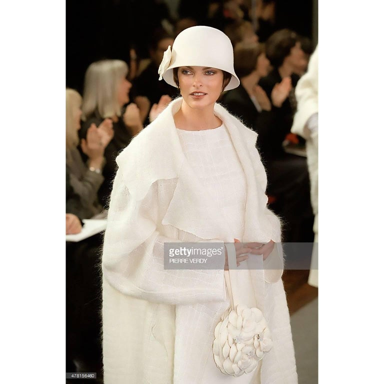 This Chanel coat is from Chanel's Autumn Winter 1998 collection and the same style was modeled by Linda Evangelista on the runway.  The coat is loosely woven in a cream wool and mohair blend and because it has such an airy, lightweight feel,  it