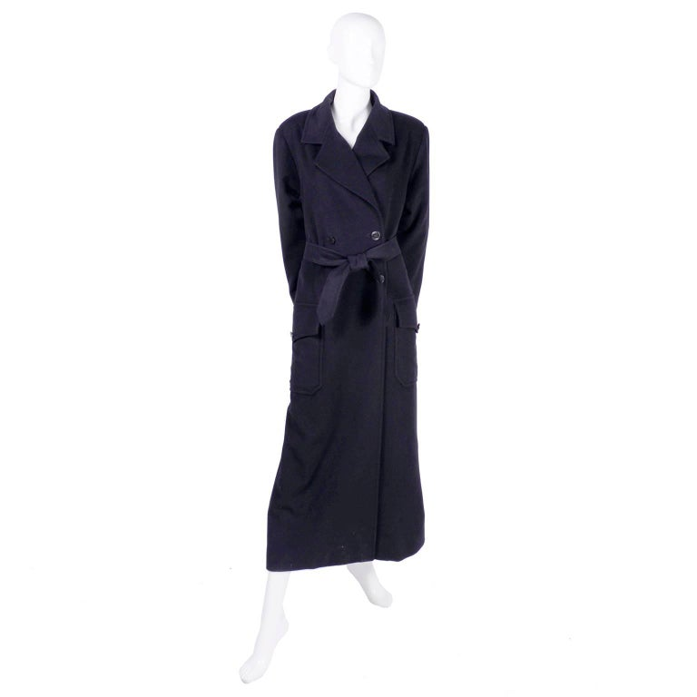 This is a gorgeous, classic Chanel double breasted coat in black wool and cashmere with  Chanel monogram buttons and matching belt.  The coat has front patch pockets that button and is fully lined in silk. The coat is labeled a size 34 but can fit