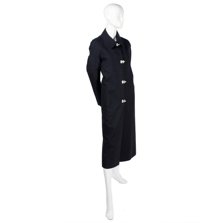 This is a great black raincoat from Celine in 91% cotton and 9% Polyuretha that was made in France.  This great coat has front Slash pockets and metal toggle Celine marked buckle closures. This is such a great coat and so easy to wear!  The coat is