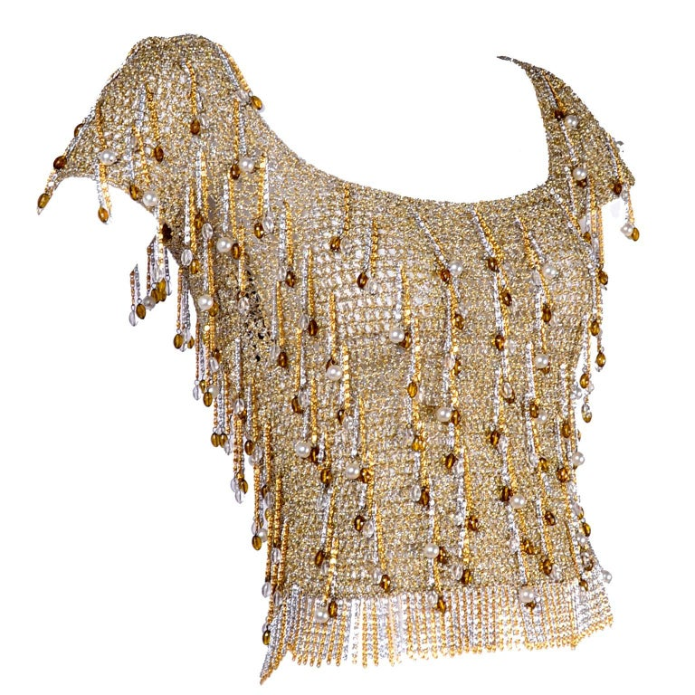 This is an absolutely  gorgeous 1970s silver and gold metallic lurex crochet top from Loris Azzaro.  This vintage short sleeve top has metal chain fringe and amber and clear beads as well as faux pearls. The top has quite a bit of stretch and is