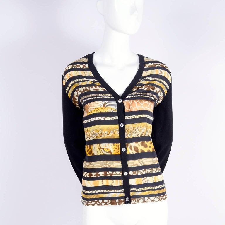 This is a Vintage Salvatore Ferragamo cotton and silk cardigan sweater with a silk scarf print in the front with animal skin prints and animal eyes! We have the coordinating  scarf with the same vertical pattern but with animal prints, hibiscus and