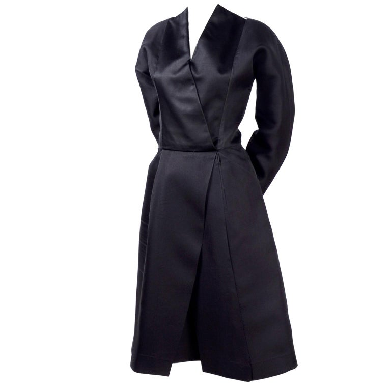 This is a late 1970's or early 1980's Geoffrey Beene New York black vintage cocktail dress with a a unique neckline and an origami style design. There are black satin panels that cross in front, meeting at the waistline to open up in two large