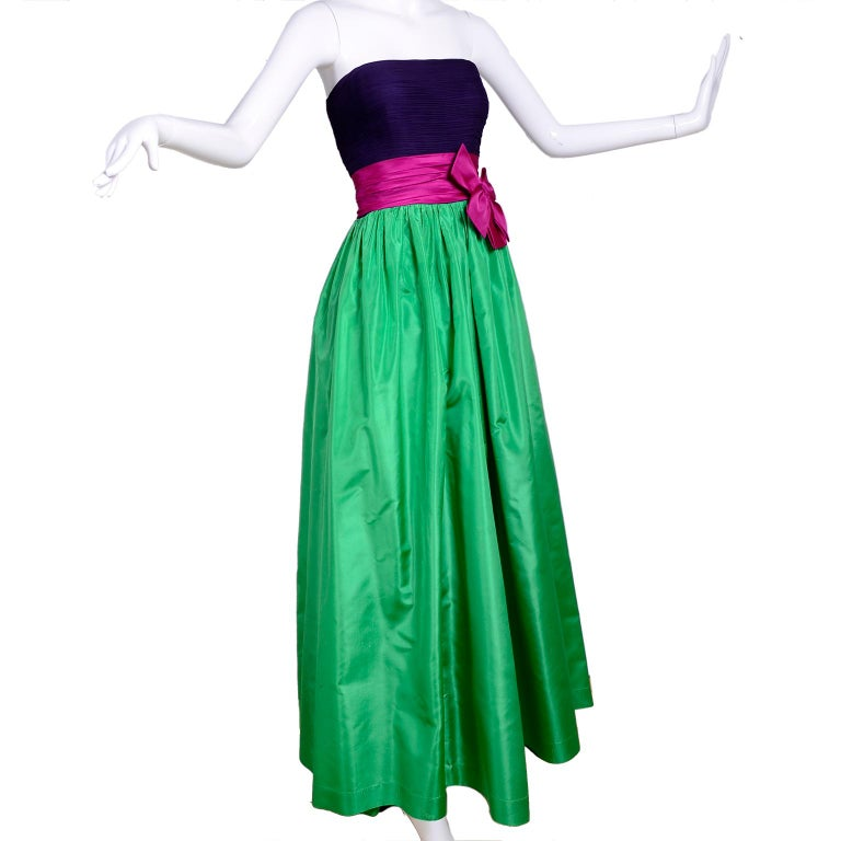 This is a beautiful Nina Ricci evening gown with a ruched deep purple silk strapless bodice. The skirt is fully lined and there is a pink satin belt with an attached bow at the waist. This is a lovely vintage dress that would be perfect for any
