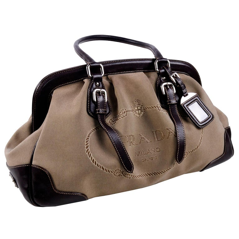 This Prada canvas jacquard and leather doctor style handbag has Prada Milano Dal 1913 on the front of canvas , and an ID tag stamped with