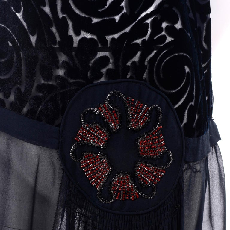 This lovely black 1920's vintage dress has a silk cut velvet bodice and a drop waist that is embellished with a beaded abstract red and gold flower.  This fabulous flapper dress has a sheer chiffon skirt and side silk panels.   These dresses are