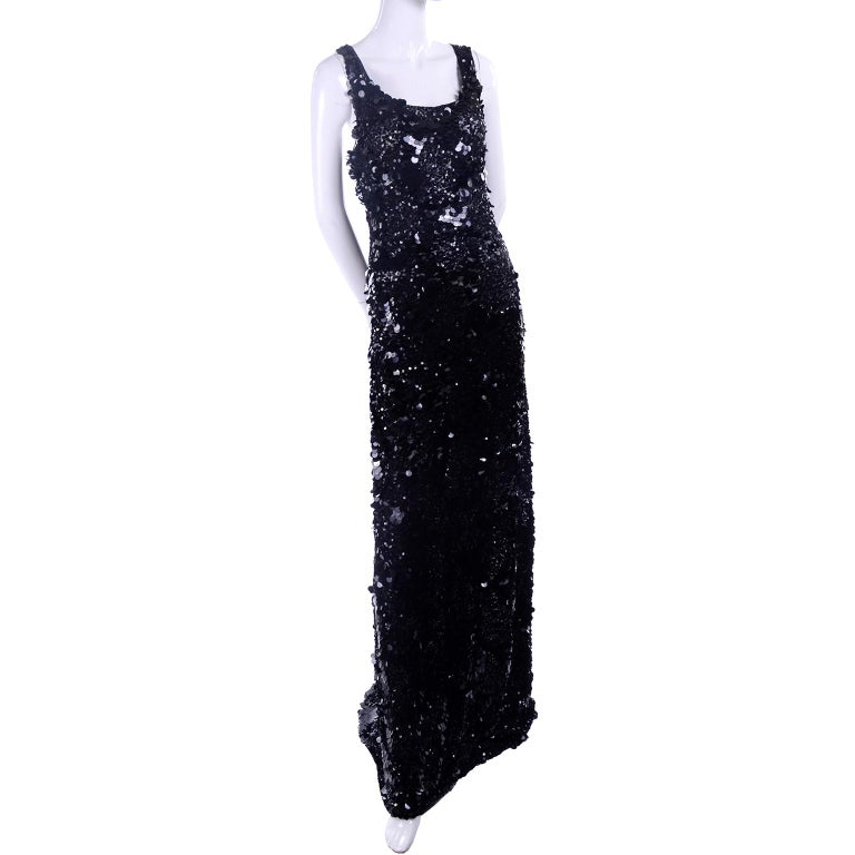 This dramatic black evening gown is made of a fine mesh net and is covered in small sequins and large paillettes. The unique thing about this incredible dress is that you can wear it as a formal evening gown with its mini train, and then bustle it