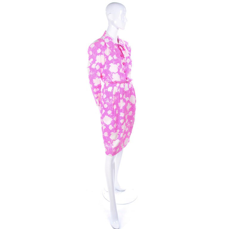 This is a lovely vintage dress from Givenchy with the Givenchy Nouvelle Boutique label from the 1980's. The dress is pink and white floral silk with tone on tone white dots embroidered all over.  The dress closes with front pink dome buttons and a