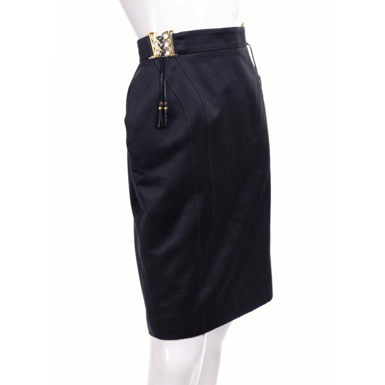 This is an unworn, new Gucci skirt with its original tags attached.  This black pencil skirt is in a luxurious semi polished cotton with rayon poly blend lining. The skirt has built in gold circle buckles that lace up with leather strings with
