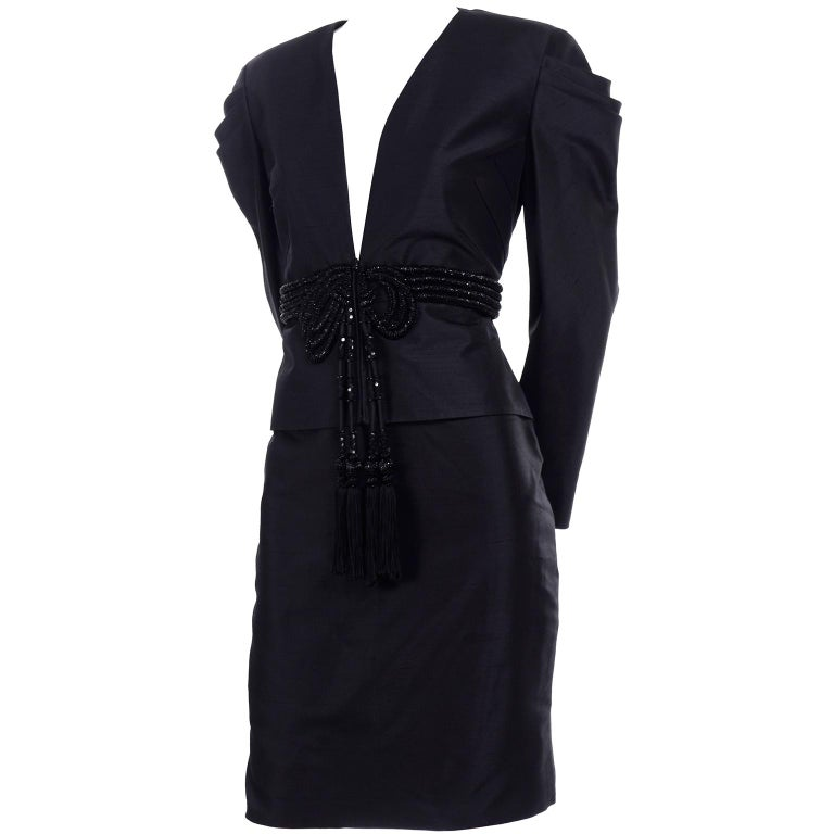This is an absolutely sensational Valentino raw silk skirt evening suit with a gorgeous blazer that has a beaded bow with tassels in the front. The jacket has a plunging neckline, wonderful inverted pleats running on the diagonal on each side in the