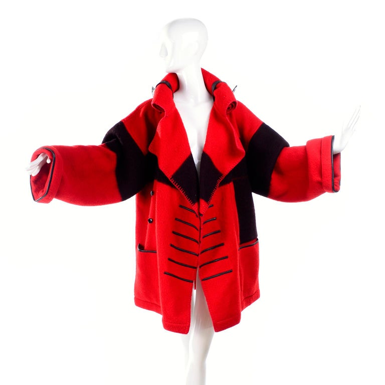This is a fabulous red and black wool vintage Jean-Charles de Castelbajac 1980s blanket coat with a pointed hood. The hood can be rolled and fastened with the leather straps similar to the way a blanket roll is secured! There are front pockets,