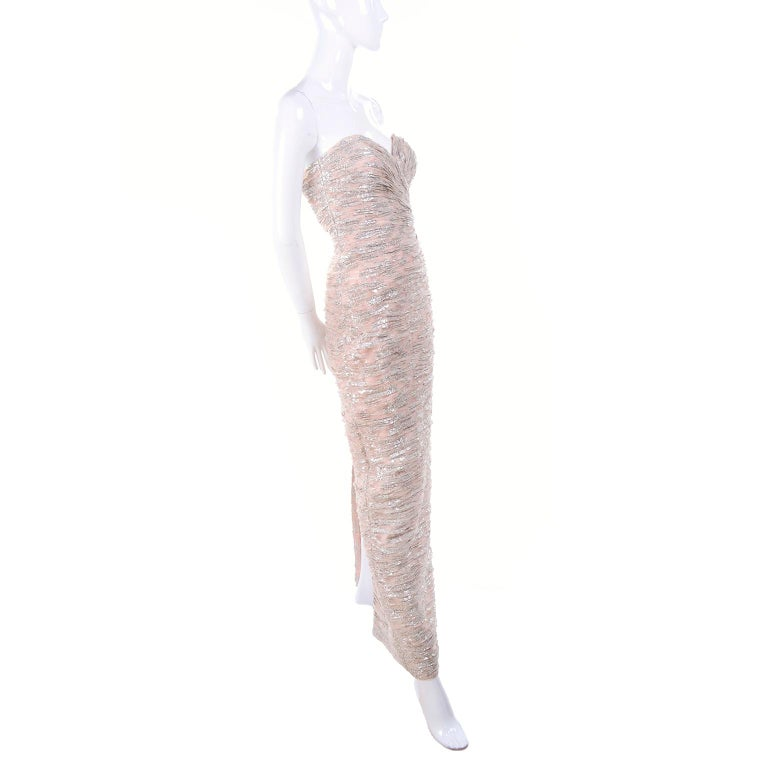 This Vicky Tiel strapless, ruchéd pale buff pink and silver metallic evening gown has a sweetheart neckline and is new with its original price tag for over $900. There is a back hidden zipper and hook and eye for closure and the dress is fully