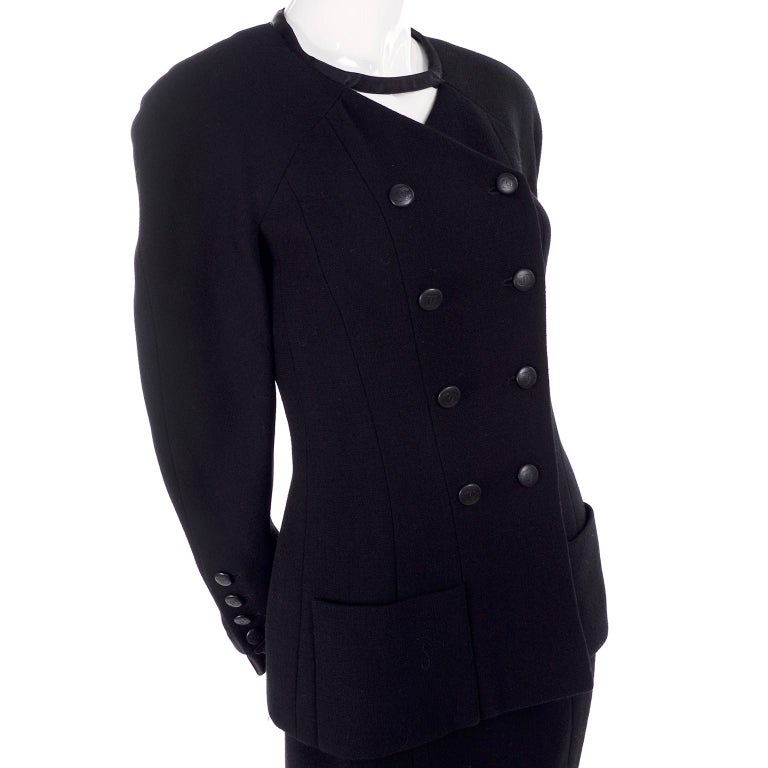 This is a wonderful vintage black wool Chanel suit designed by Karl Lagerfeld for the 1998 Cruise / Resort collection. The outfit includes a skirt and a double breasted jacket with an interesting connecting piece of fabric that crosses over at the