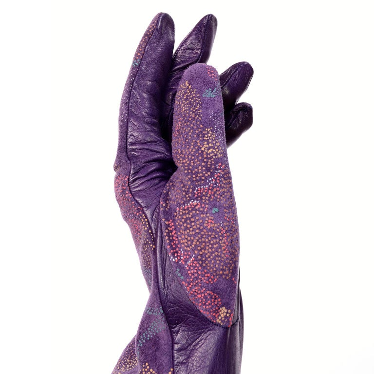 These stunning vintage leather gloves were designed by Carlos Falchi and were made in Italy. The gloves are purple leather with hand painted pointillism style flowers in purple, red, yellow, white and blue on the top side. Lined in silk, these