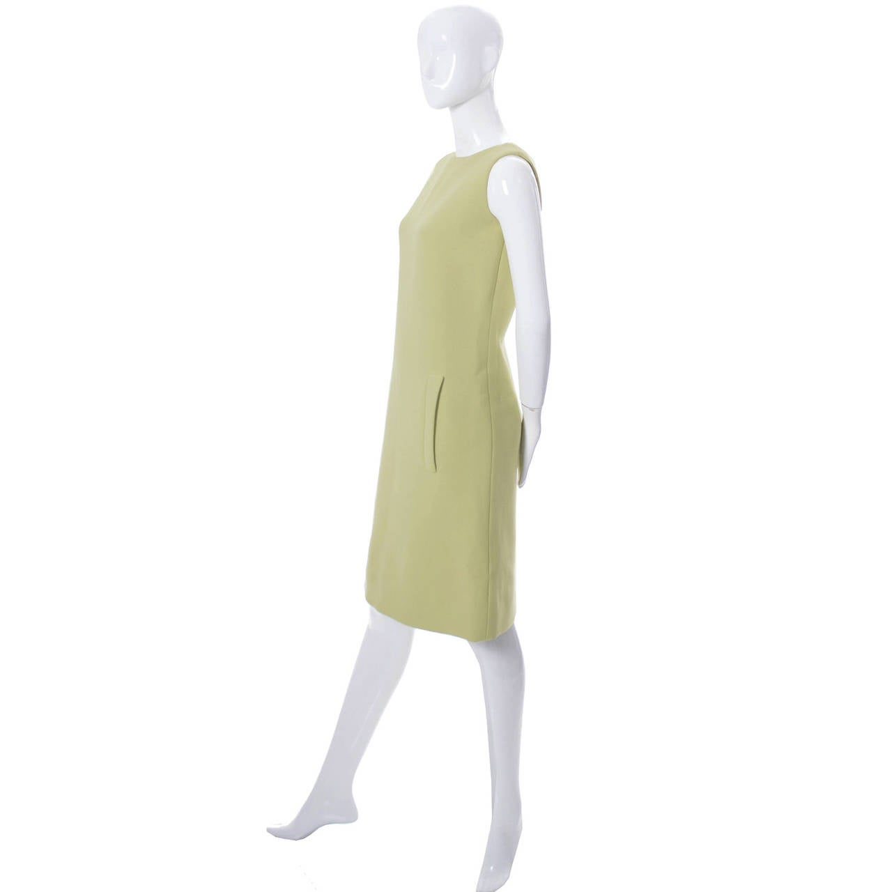 This is a vintage 1960's timeless sleeveless green shift dress from designer Norman Norell. This fully lined structured wool dress has 2 pockets in the front and 4 black buttons down the back. This dress was originally purchased in the late 1960's