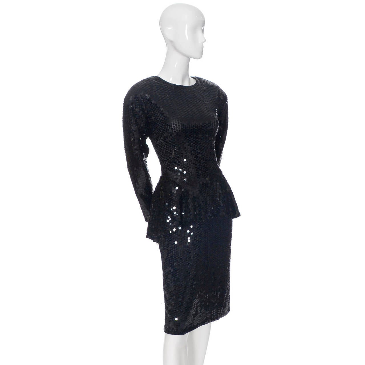 This is a fabulous classic vintage 1980's Oleg Cassini dress covered in black sequins. The dress has long sleeves, a back zipper and a beautiful peplum. The shoulder pads are attached but not sewn in so they could easily be removed if you prefer.