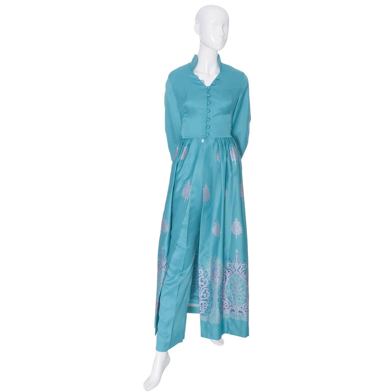 This is a 2 piece vintage outfit from Alfred Shaheen that was never worn. Purchased in the 1970's, this pretty turquoise blue ensemble includes an over dress with a split skirt in the front that reveals high waisted pants with back zipper