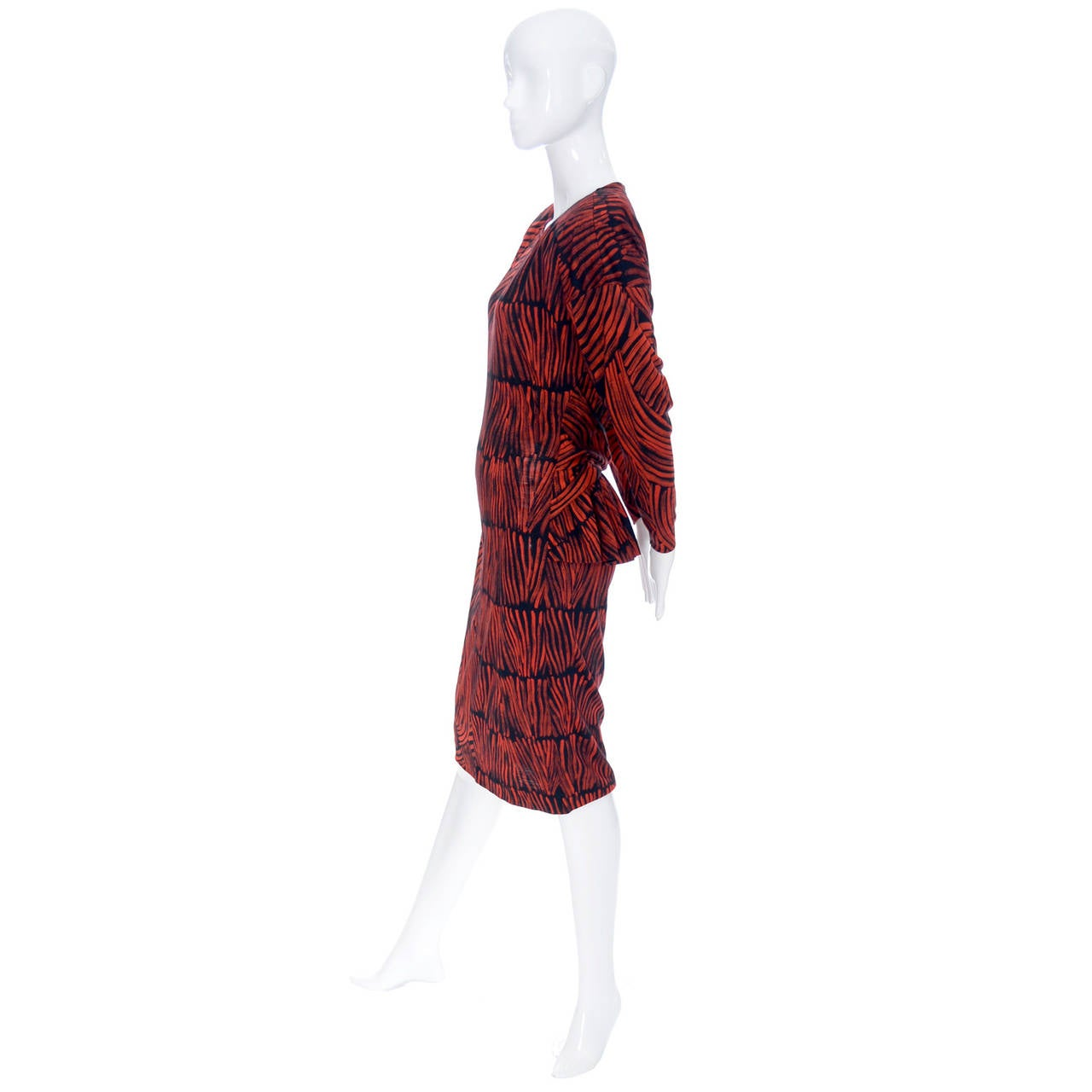 I love the fabulous abstract red and black print on this lightweight wool vintage Missoni dress! The dress was made for I Magnin in the 1980's and it has a great ruffled peplum in the back with an attached cross over sash. There are shoulder pads,