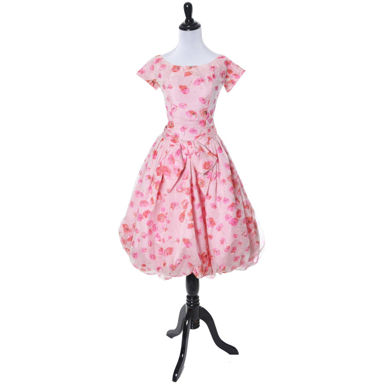 This pretty pink floral vintage dress is from the 1950's and was made by Suzy Perette, New York. The dress has a bubble skirt and a wonderful bow below the waist. The dress is in a sheer poppy floral organza over pink taffeta with a back zipper.
