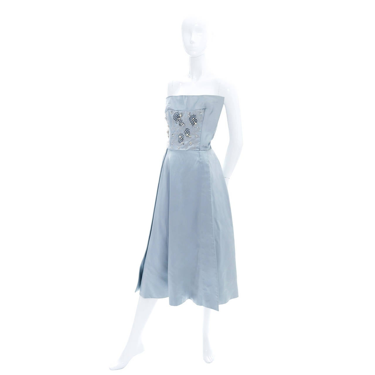 This is a gorgeous vintage blue satin cocktail dress from Harvey Berin, designed by Karen Stark.  This dress has an incredible, heavily beaded bodice that includes seed pearls, beads, rhinestones, and larger pearls. The bodice is so unique with one
