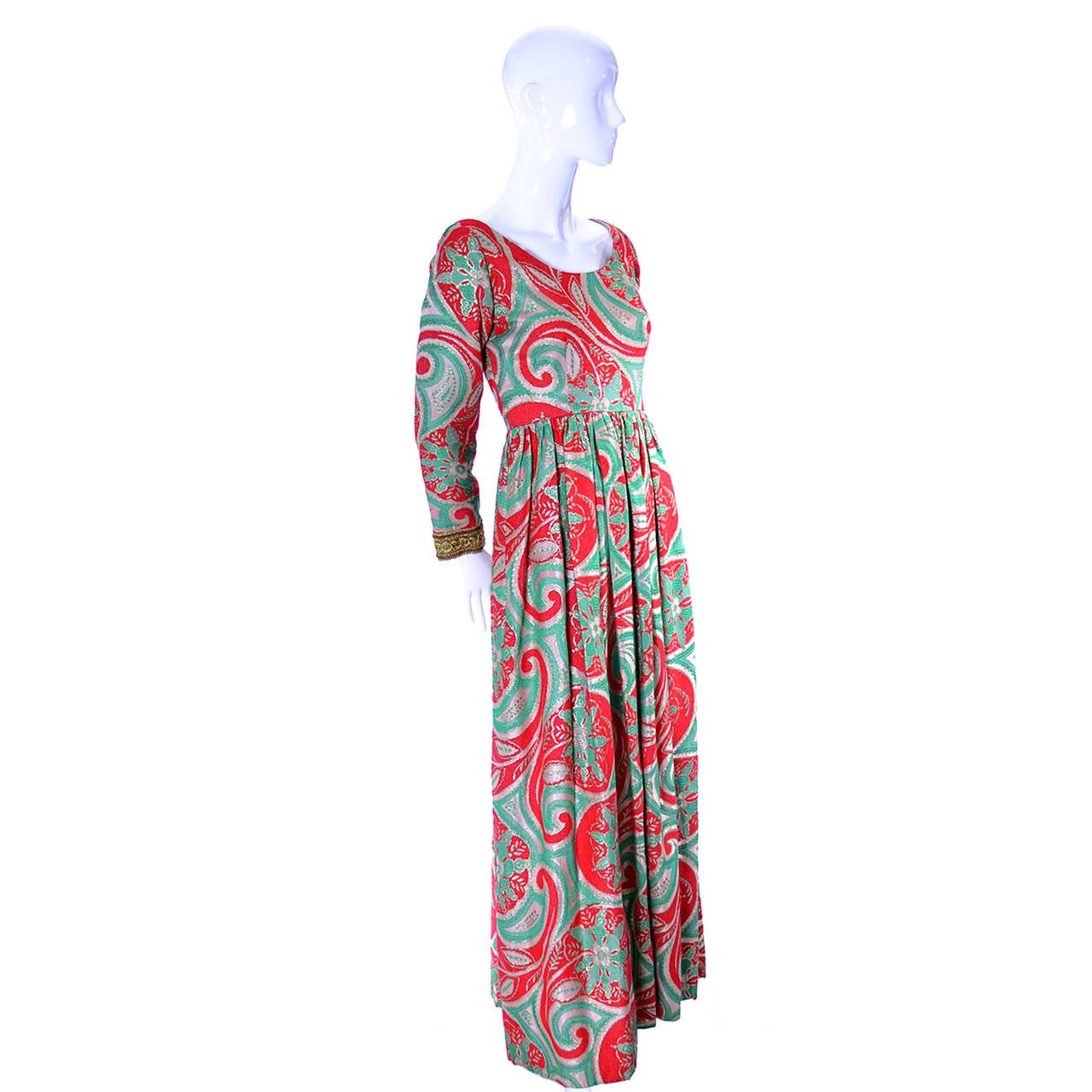 This is a rare vintage Oscar de la Renta boutique 1960s maxi dress. This gorgeous full length dress is fully lined and the fabric feels like a wool and has silver metallic threads woven in the paisley pattern in shades of gold, red, green and pale
