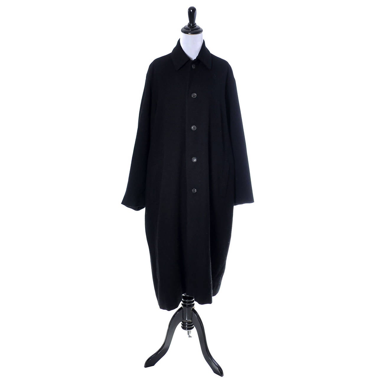 This is a late 1980's or early 1990's black wool coat from Yohji Yamamoto.  This beautiful coat is almost a cocoon style with buttons up the front and oversized fit.  There is a back center slit at the bottom, and the coat is in as new condition.