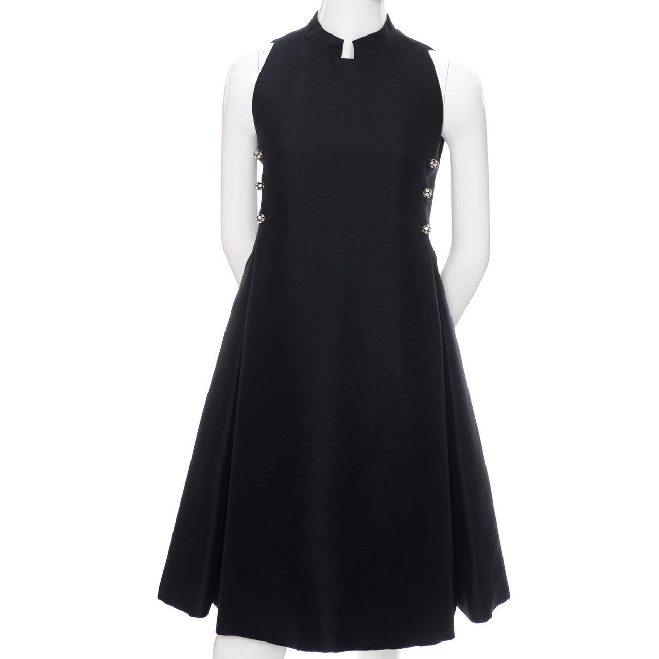 Geoffrey Beene minimalist vintage dresses are some of my very favorites and this one is wonderful.  This black sleeveless midi dress has beautiful rhinestone buttons, a cut out mandarin style collar, and double pleated skirt.  This baby doll empire