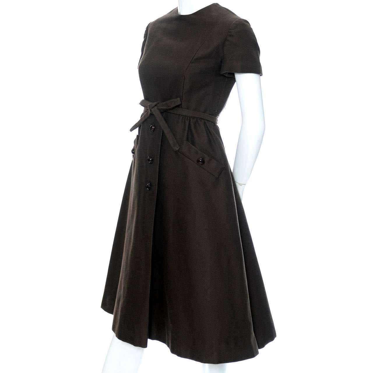 This rare vintage dress from Geoffrey Beene is from the 1960's and has decorative front buttons, a fabric belt, and great front pockets. The brown pique cotton dress has a full skirt, a back zipper and is fully lined. We love Geoffrey Beene, his