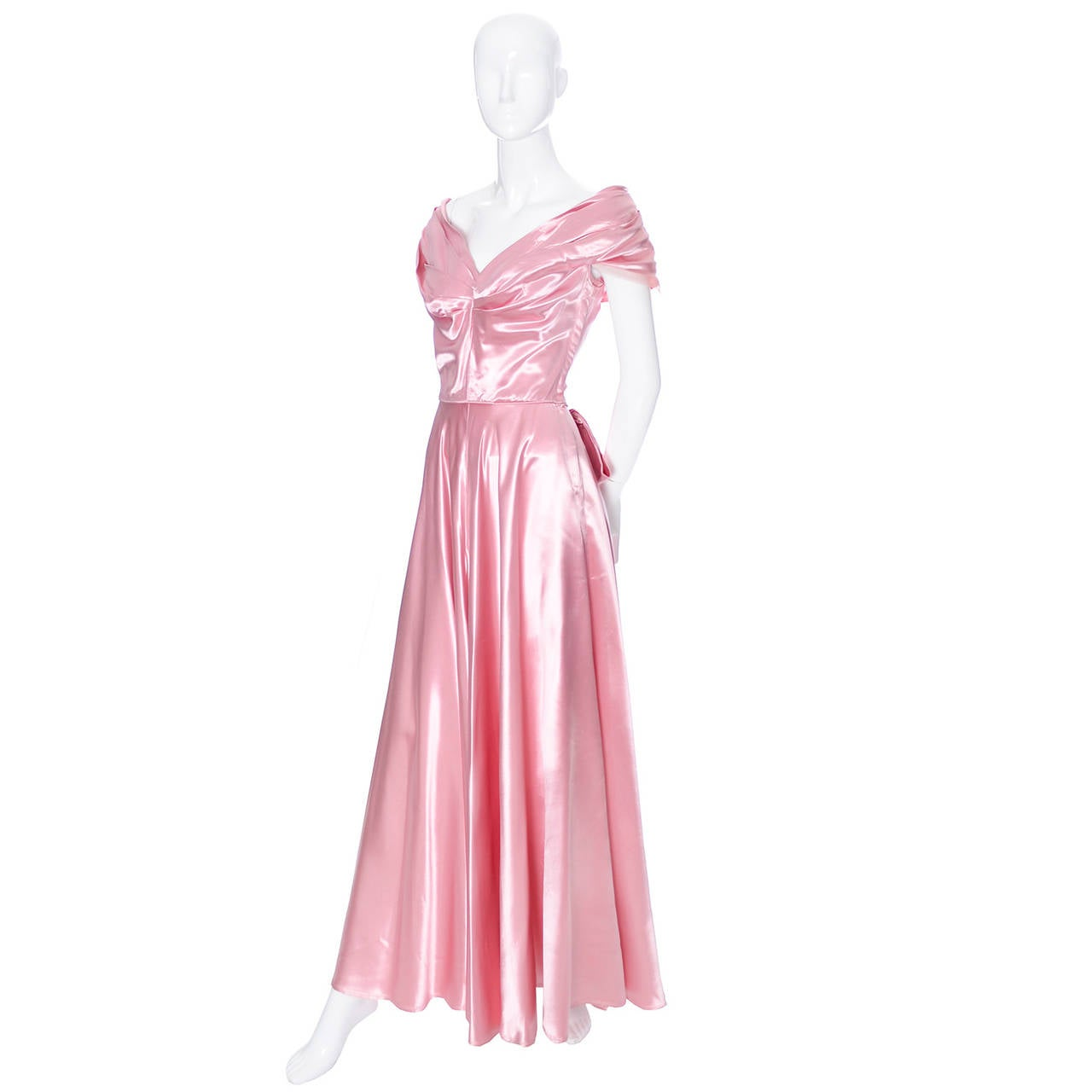 Luxe vintage evening gown from Emma Domb from the late 1940s in a beautiful shade of pink. This dress is in excellent condition and has pretty net trim on the semi off-shoulder pleated shawl collar.  There is a side metal zipper and a double