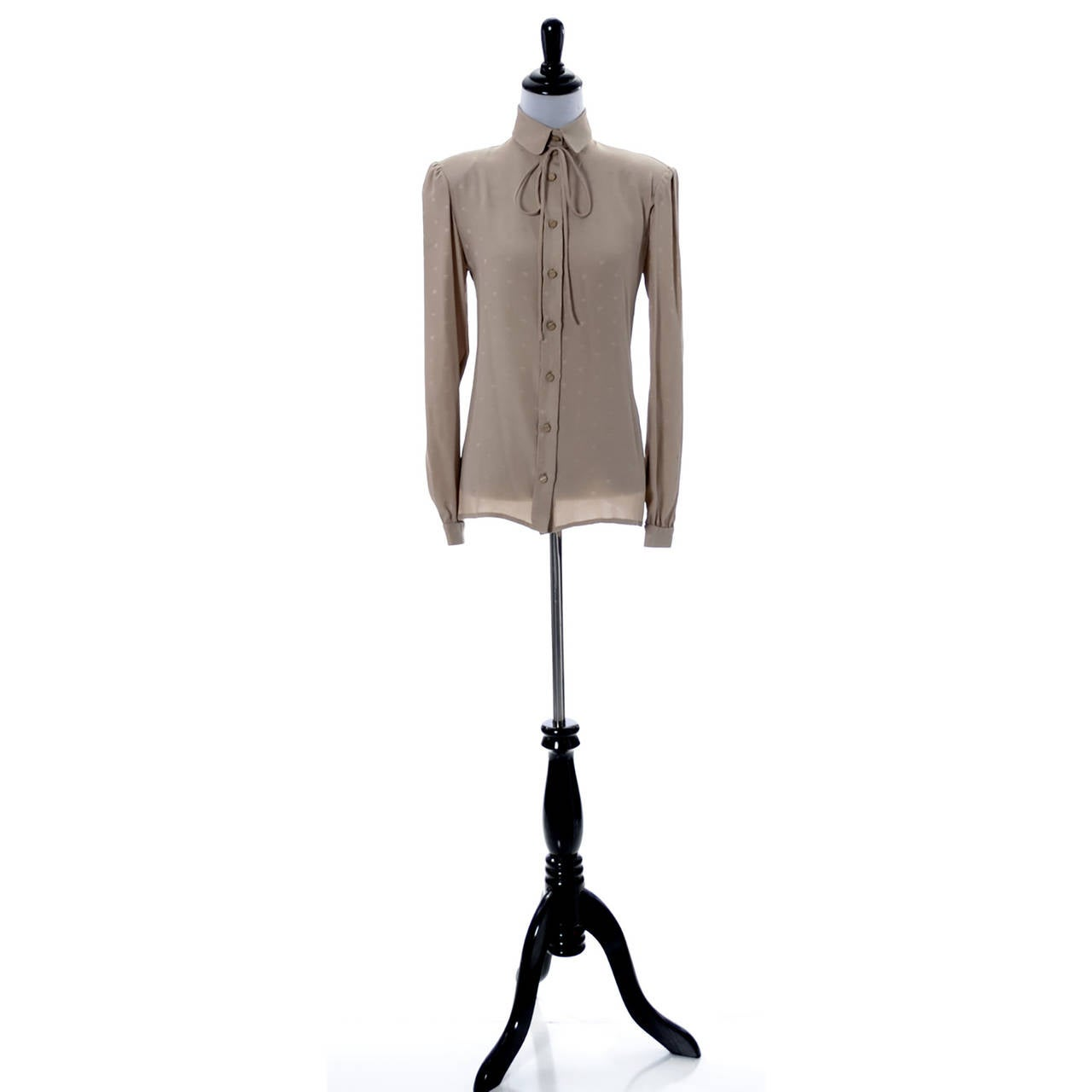 This is a classic, beautiful vintage Valentino silk blouse in tan/taupe with a Valentino V logo tone on tone pattern.  There is a fabric tie at the neck and this top is in mint condition.  This blouse was made in Italy, and I would estimate this to