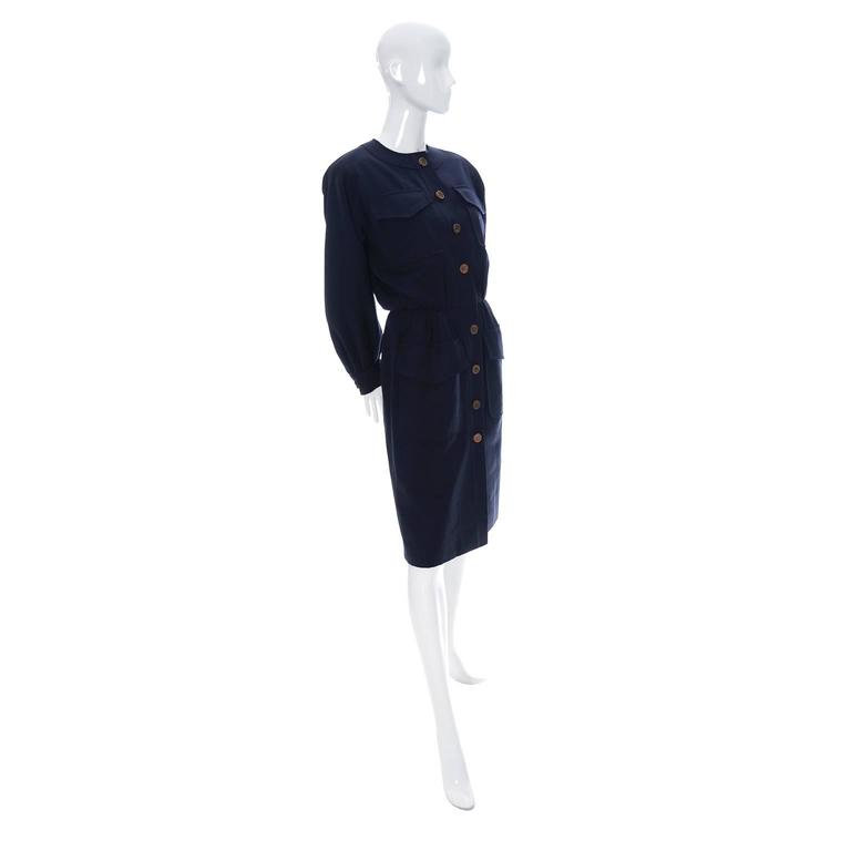 This is a classic vintage dress from YSL in navy blue wool with wood buttons and 4 front pockets. This dress is in excellent condition, has the Yves Saint Laurent Rive Gauche label and is from the 1980's. The dress is lined and is labeled a size 40.