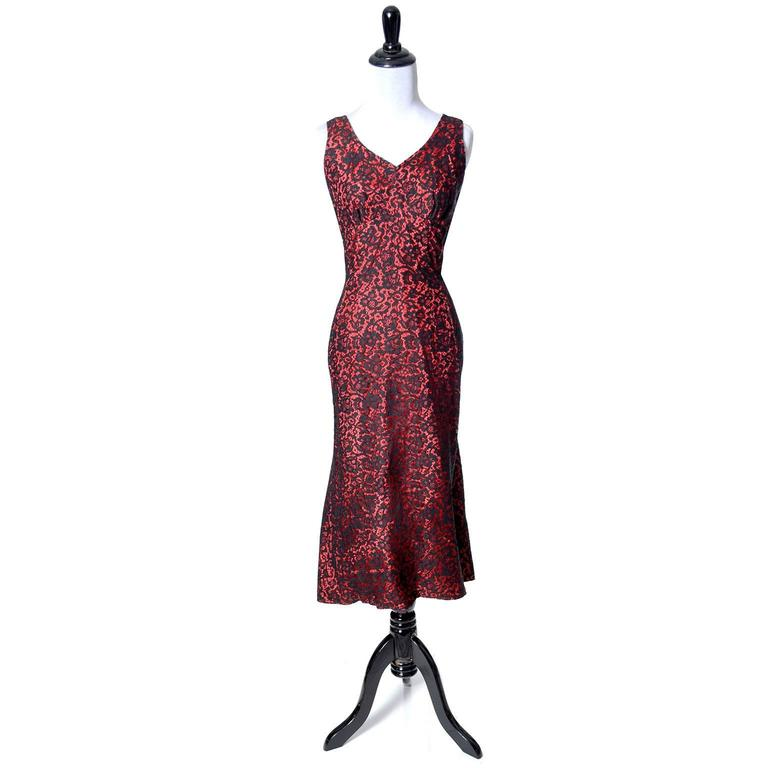 """This is a fab vintage 1950s designer dress from Emma Domb. This beautiful early 50s dress is sleeveless, with a fun skirt that looks almost like a fish tail hem in the back. The dress is red taffeta with black lace overlay and opens with a 13"""" side"""