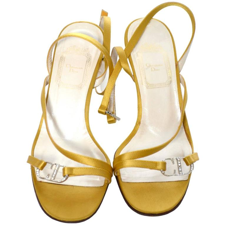 This is a very pretty pair of Christian Dior shoes / heels in a gold satin with rhinestone CD logo clasp at the ankle and on the toes.  These shoes are labeled a size 36 (approximately a US size 6), and have barely, if ever, been worn.  The sole is