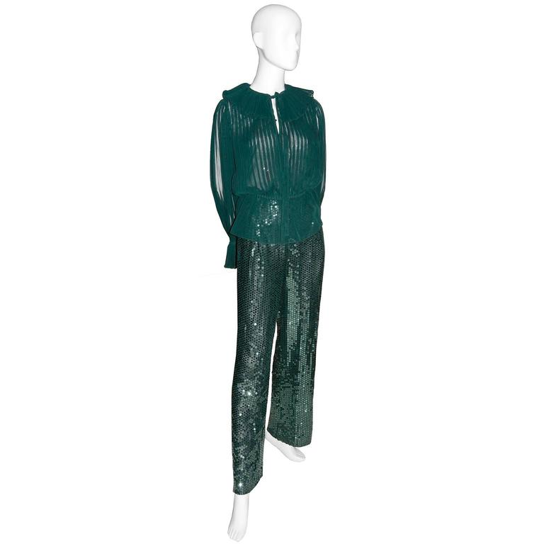 This pretty vintage Oscar de la Renta 2 piece outfit includes a pair of high waisted sequin pants and a beautiful pleated blouse with keyhole bodice opening that ties and poet sleeves with pleated ruffles.  This outfit can be worn with the peplum of