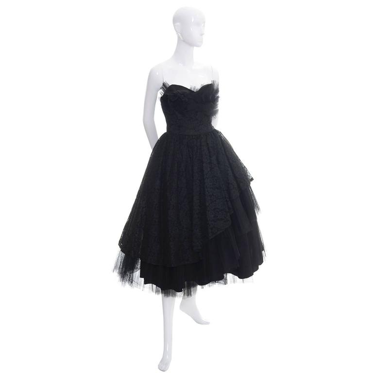 This 1950's vintage strapless party dress from Emma Domb is such a classic!  The taffeta under skirt is covered with diagonal rows of lace and tulle.  There is a side metal zipper and there are stays in the bodice.  I estimate this dress to be a