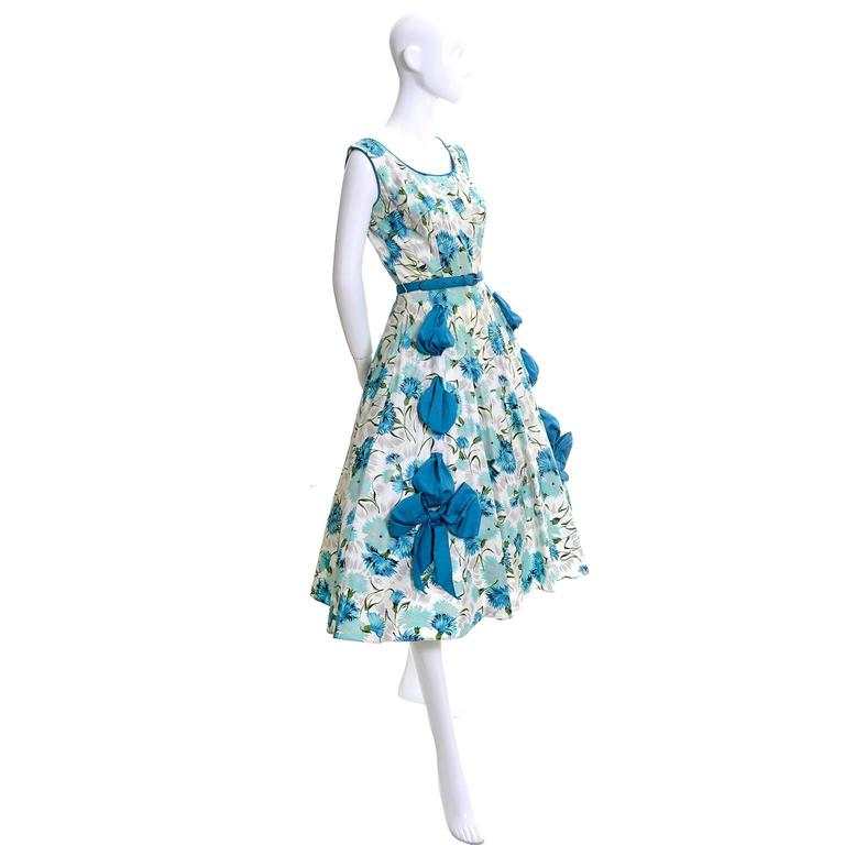 This is a fabulous 1950's vintage party dress with gorgeous rhinestones and beautiful wide blue ribbons that are threaded through the skirt of the dress and tied in bows at the end.  The sleeveless vintage 50's dress has a side metal zipper and its
