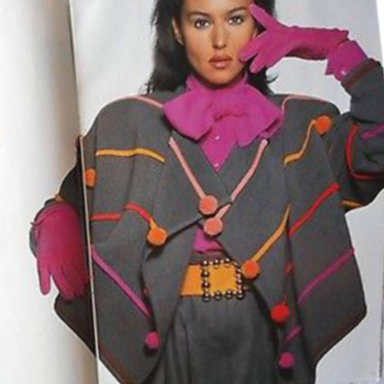 This is such an incredible vintage 100% wool Sweater from Escada!  The sweater is gray ribbed wool with multi colored knit trim that is embellished with  pom poms in the same colors!  The sweater is labeled a 40 and was designed by Margaretha Ley