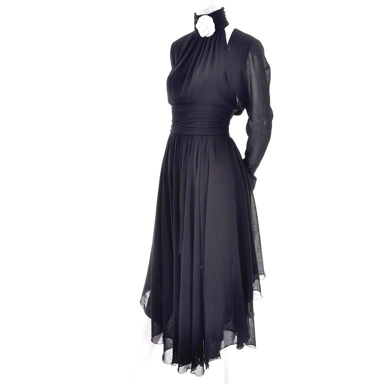 This is an absolutely gorgeous vintage Chanel lightweight black wool crepe dress labeled a size 36 with a simple matching bolero jacket. (The dress and bolero are a true black, a few of the photos have been lightened to show more detail). The dress