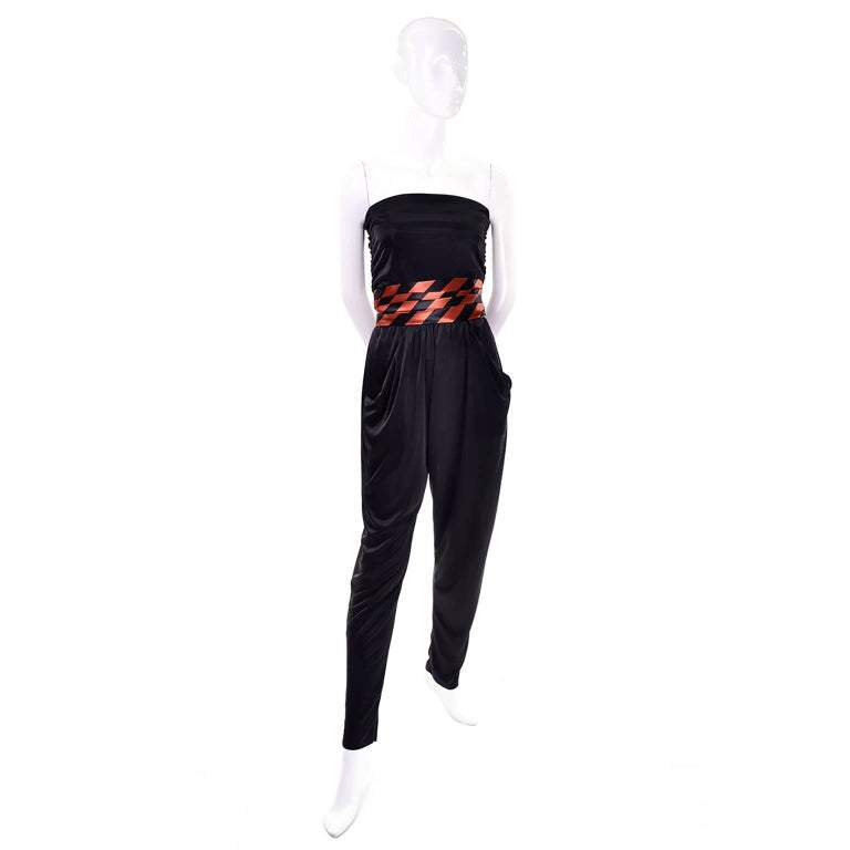 This 1970's vintage jumpsuit with a coordinating orange and black satin striped jacket and cummerbund is perfect for any Halloween or Fall party! The slinky black jersey jumpsuit is strapless with an elastic waist and slips on with no closures. The