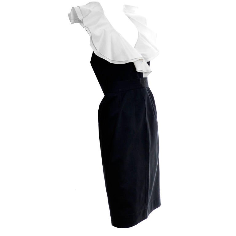 This is a black cotton 2 PC YSL dress has a pretty double layer of white ruffles at the collar. This outfit from Yves Saint Laurent has a button front sleeveless top that is labeled a size 36 and a slim skirt with zipper and hook and eye and side