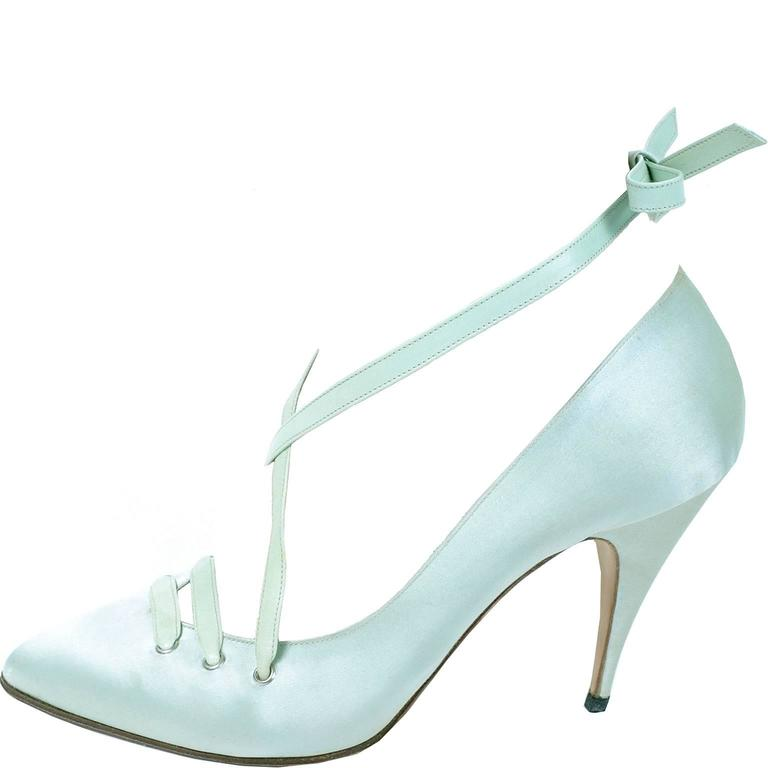 """These pretty green satin Manolo Blahnik shoes have 4"""" heels and fabulous leather laces that become ankle straps. The shoes are marked a size 39 and were made in Italy in the 1980s."""