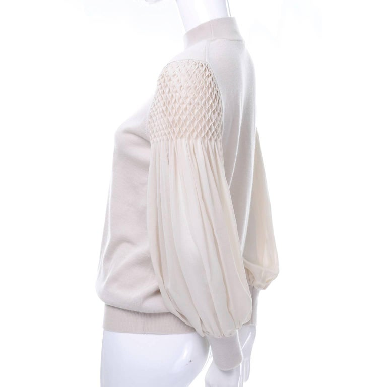 This gorgeous bone or sand colored cashmere sweater is by Luis Vuitton.  The sweater has beautiful puffy silk bishop sleeves that have smocking at the shoulders. There is waffle elastic at the hem, cuff, and neckline. This top was made in Italy and
